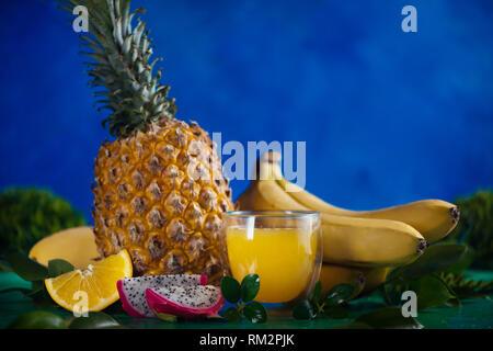 Jus frais de fruits tropicaux sur un fond bleu avec les bananes, ananas, mangue et fruit du dragon. Verre coupe avec copie espace Banque D'Images