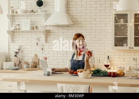 Belle jeune fille rousse avec de grandes boucles d'organiser un poivron rouge dans sa main Banque D'Images