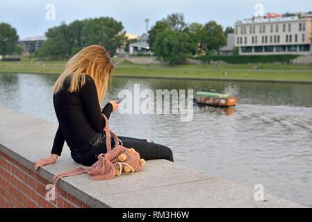 Jeune fille assise sur le parapet du trottoir le long de la Vistule, au pied du château de Wawel, province de Malopolska (Petite Pologne), Banque D'Images