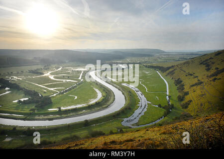 Ingelmunster, East Sussex, UK. Feb 13, 2019. Le soleil s'élève au-dessus de la rivière Cuckmere qui serpente à travers le Parc National des South Downs. Crédit : Peter Cripps/Alamy Live News Banque D'Images