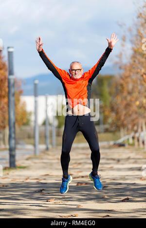 Runner Senior man jumping les bras après l'exécution Banque D'Images