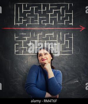 Femme perplexe en face de tableau noir à la recherche jusqu'à trouver une solution pour échapper à labyrinthe. Young businesswoman d'enfreindre les règles, comme une ligne rouge pie Banque D'Images