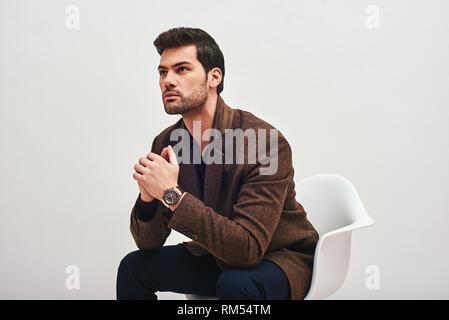 Close up le chic de l'homme aux cheveux noirs portant des pantalons bleu et marron, avec une veste cher montre sur son poignet, assis sur une chaise blanche, ses mains et à l'écart Banque D'Images