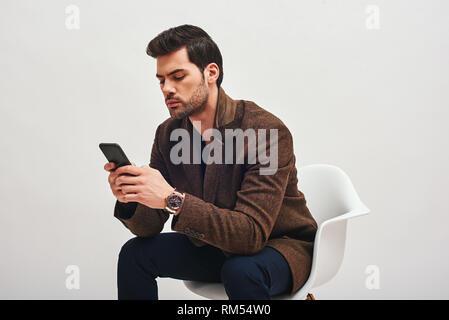 Close up le chic de l'homme aux cheveux noirs portant des pantalons bleu et marron, avec une veste cher montre sur son poignet, assis sur une chaise blanche et en regardant son téléphone Banque D'Images