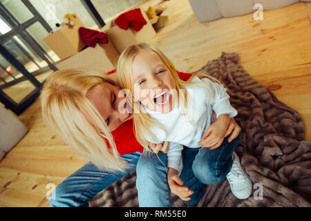 Cheerful blonde girl laughing tandis que chatouillement Banque D'Images