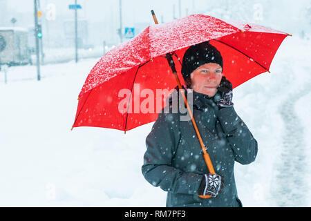 Worried Woman talking on mobile phone dans la neige à l'extérieur sous parapluie rouge Banque D'Images