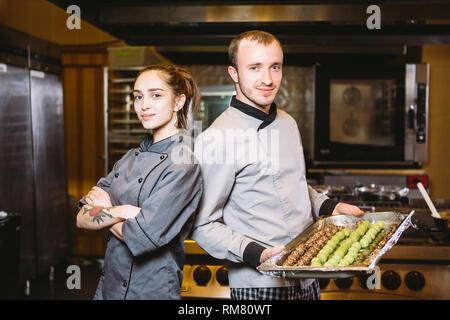 Préparation de la profession des confiseries. Man and Woman deux employés collègue d'équipe pastry chef posing à huis clos en uniforme je Banque D'Images