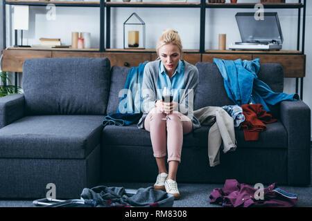 Appuyée femme assise avec verre de vin rouge tandis que l'emballage dans la salle de séjour après sa rupture avec petit ami