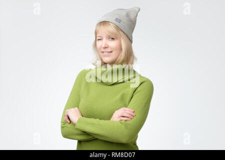 Cheerful young beautiful girl in green chandail et clignant de l'hat smiling Banque D'Images