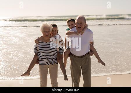 Heureux grands-parents aux petits-enfants de ferroutage donnant sur la plage Banque D'Images