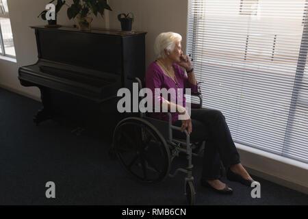 Vue de côté mobilité senior woman sitting sur fauteuil roulant et à l'extérieur à travers la vitre Banque D'Images