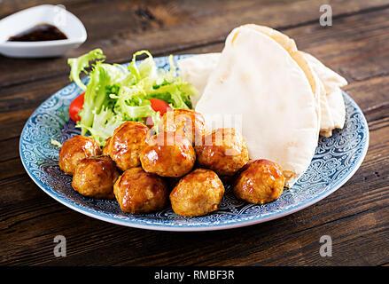 Boulettes de viande à la glaçure aigre-doux sur une plaque avec du pain pita et de légumes dans un style marocain sur une table en bois. Des tapas. La tendance. Banque D'Images