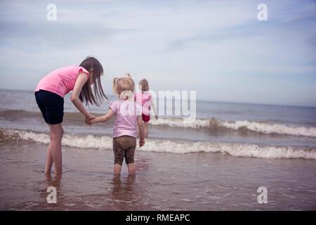 Trois enfants pagayage dans de petites vagues sur le rivage de la mer du Nord Banque D'Images