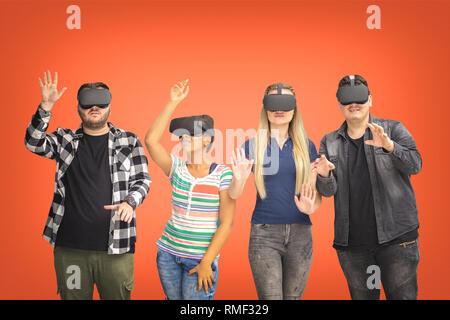 Groupe d'amis multiraciale jouant sur des lunettes vr isolé sur bachground de corail. Le concept de réalité virtuelle avec les jeunes de s'amuser ensemble connexion