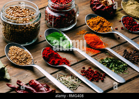 Bande d'assorted spices placés en ordre sur le bois de la table près de bouteille d'huile Banque D'Images