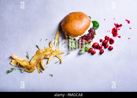 Burger de boeuf, confiture de canneberges et fromage à la crème. Frites avec du romarin. Vue de dessus, copiez l'espace. Banque D'Images