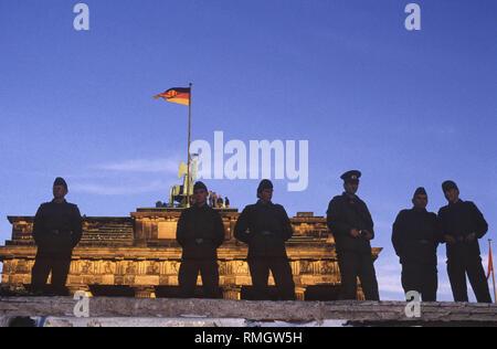 Des milliers de Berlinois de l'Ouest et l'Est de célébrer l'ouverture de la frontière le Mur de Berlin à la porte de Brandebourg. Gardes-frontière de la RDA d'empêcher les gens d'entrer dans la zone réservée à la place en face de la porte de Brandebourg et la Pariser Platz. Banque D'Images