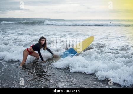Jeune fille en bikini - surfer avec des lignes blanches sur son joli visage masque surf board plonger sous l'eau avec plaisir sous les grandes vagues de l'océan. Vie de famille Banque D'Images