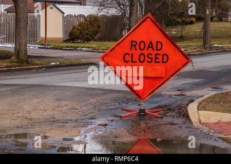 La fermeture des routes en forme de losange orange sign on road dans un quartier près d'une maison. Le signe est dans une flaque d'eau sur la route Banque D'Images