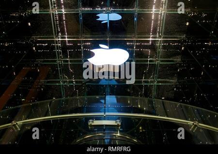 Le logo blanc d'Apple à un magasin phare à New York City's 5th Avenue la nuit. Banque D'Images
