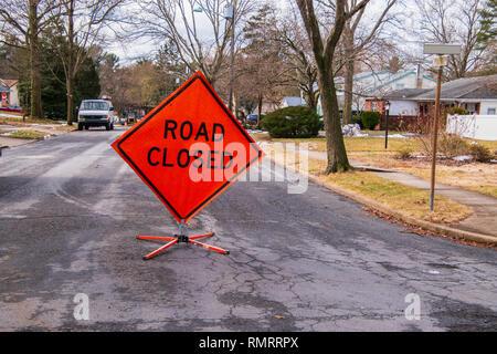 La fermeture des routes en forme de losange orange sign on road dans un quartier près d'une maison. Banque D'Images