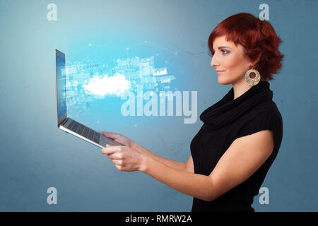 Woman holding laptop projetant des notifications, des symboles et de l'information fondée sur un système de technologie de l'informatique en nuage Banque D'Images
