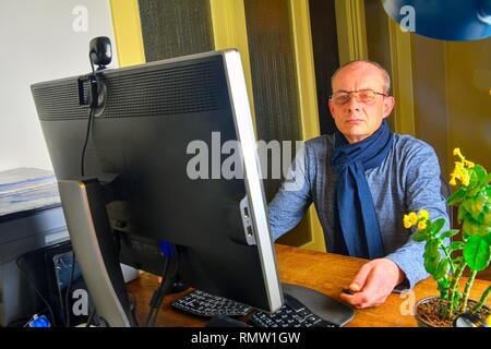 Homme d'âge moyen avec des lunettes assis à un bureau. Homme mûr à l'aide de l'ordinateur personnel. Concept principal. Man working at home office Banque D'Images