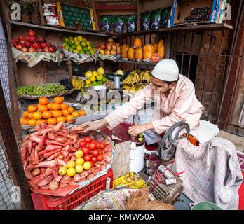 AGRA, Uttar Pradesh, Inde - 24 février, 2015: musulman de faire du jus de carotte frais dans son atelier sur le Taj Ganj Street Banque D'Images