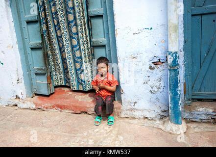 AGRA, Uttar Pradesh, Inde - février 24, 2015: Petite jeune Indien assis près de sa maison à la porte étroite rue de Taj Ganj district. Banque D'Images