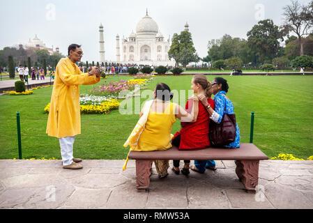 AGRA, Uttar Pradesh, Inde - 24 février, 2015: la famille indienne de prendre photo de groupe avec Affaires en robe rouge sur le banc dans le jardin en face de Taj Banque D'Images