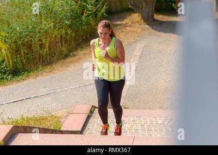 Portrait d'une femme d'âge moyen d'exécution au moment de la montée des escaliers au cours de cardio plein air dans une journée ensoleillée de l'été Banque D'Images