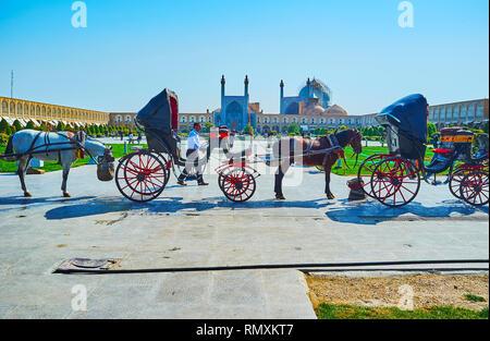 ISFAHAN, IRAN - le 21 octobre 2017: La ligne de calèches à Naqsh-e Jahan Square avec une vue sur la Mosquée Shah historiques et d'arcades de Grand Banque D'Images