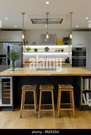 Intérieur d'une cuisine moderne montrant une île et les tabourets.