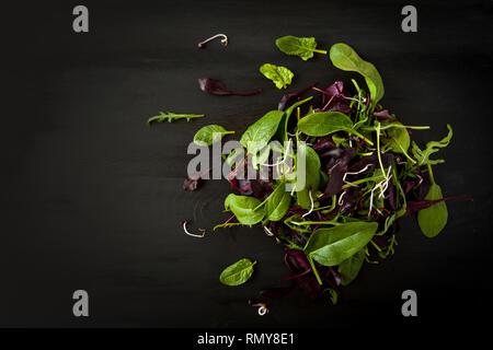 Detox de printemps mélange Salade de roquette, betterave, épinard et pousses sur planche de bois sombre sur fond noir, vue du dessus. Banque D'Images