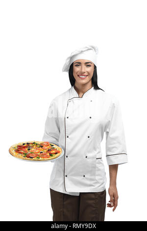 Portrait de jeune femme aux cheveux noirs qui tiennent de la nourriture et d'attente pour les clients. Belle nouveau chef du restaurant à vêtements de travail avec célèbre pizza. Heureux et souriant pizzaiolo aimer son travail. Banque D'Images