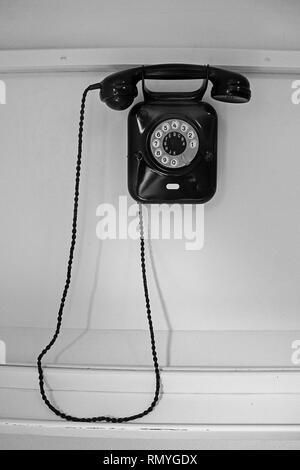 Vieux téléphone noir accroché sur mur blanc Banque D'Images