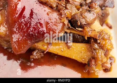 Close-up of a popular espagnol lave croustillant de Pata, viande de porc cuit encore sur les os, avec sauce glaced