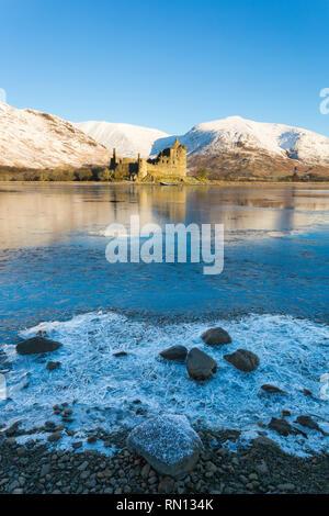 Tôt le matin, au château de Kilchurn et Loch Awe, Argyll and Bute, Ecosse, ROYAUME UNI sur une journée d'hivers froids avec de la neige et le loch congelé