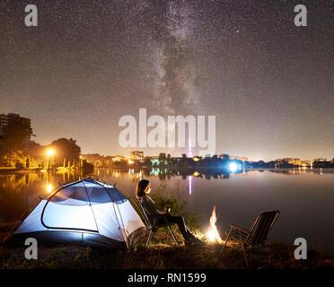 Nuit de camping sur le lac rive près de camp,'tente. Femme avec tasse de café assis sur une chaise près d'une autre chaise vide, profitant de soir ciel plein d'étoiles et Milky Way, les lumières de la ville, sur l'arrière-plan Banque D'Images