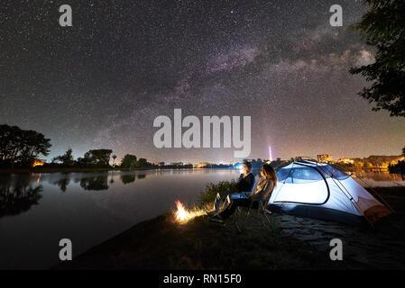 Nuit camping à bord du lac. L'homme et la femme assis sur des chaises près de bonfire et incandescent tente, enjoying view de soir ciel plein d'étoiles et Milky Way, surface de l'eau calme, lumineux ville sur l'arrière-plan. Banque D'Images
