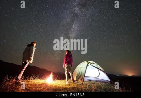Couple heureux randonneurs ayant un reste d'été au camping de nuit dans les montagnes. Jeune homme et femme debout à côté de feu de camp, allumé'tente sous beau ciel étoilé ciel plein d'étoiles et Milky Way Banque D'Images