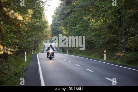 Motorbiker dans casque et vêtements de cuir noir moto puissante moderne d'équitation le long de la route asphaltée entre les enroulements de hauteur des arbres verts par beau jour d'automne. Banque D'Images
