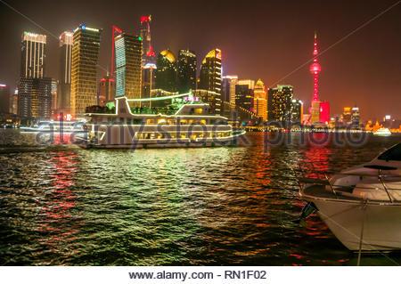 Occupé à Huangpu River scène avec un bateau passant entre un yacht de luxe et de l'allumé Pudong skyline. Banque D'Images
