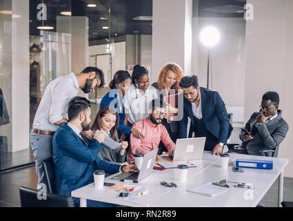 L'interracial deux gars dans le travail de bureau usure formelle jouer jeu en ligne sur les ordinateurs portables pendant que leurs collègues joyeux excité réunir autour de la table supp Banque D'Images