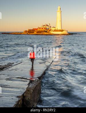 Un homme se tient sur l'île de St Mary's Causeway tandis que le soleil couchant illumine St Mary's phare sur la côte de Whitley Bay à Tyneside. Banque D'Images
