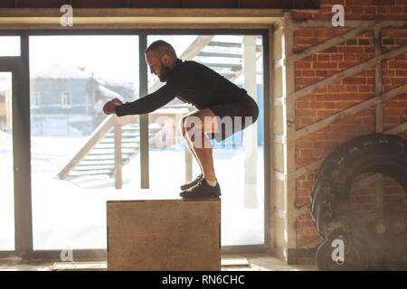 Fort jump plyo exercice - young caucasian man doing entraînement fonctionnel à la salle de sport bien éclairé dans une journée ensoleillée, motion tourné en phase d'atterrissage. Banque D'Images