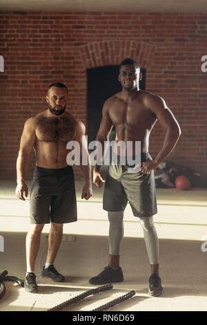 Deux hommes torse nu multiethnique avec bodybuilders corps musculaire parfait posent contre un mur de briques Banque D'Images