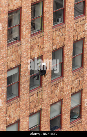 Ingénieur industriel descendre en rappel le long du côté d'un immeuble sur l'inspection des structures, New York City, USA Banque D'Images