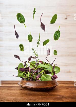 Explosion de la salade de roquette, betterave, épinard et pousses sur un parquet en bois sur fond blanc, vue du dessus. Banque D'Images