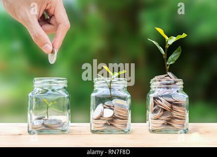 L'épargne, l'investissement de l'argent, gagner de l'argent pour l'avenir, la gestion de patrimoine financier concept. Un homme hand holding coin sur pièces empilées dans un bocal en verre et g Banque D'Images